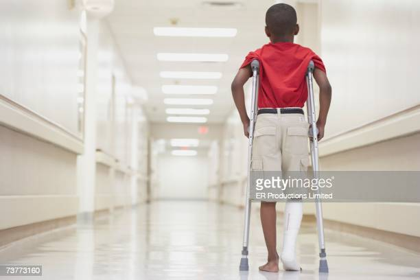 African boy with broken leg walking on crutches