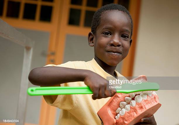 African boy with dentures and toothbrush