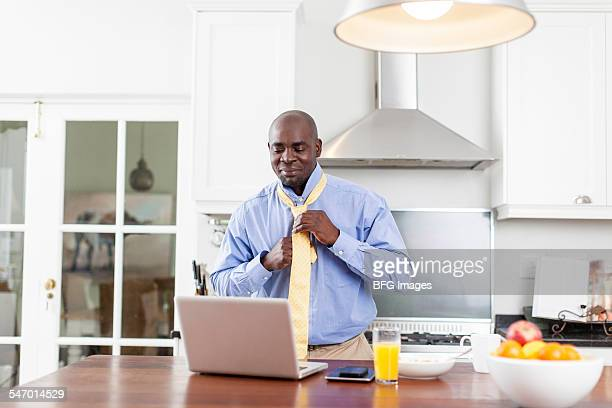 African business man using laptop in kitchen during breakfast and adjusting tie , Cape Town, South Africa