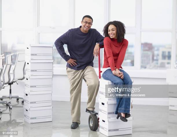 African business people with boxes in new office