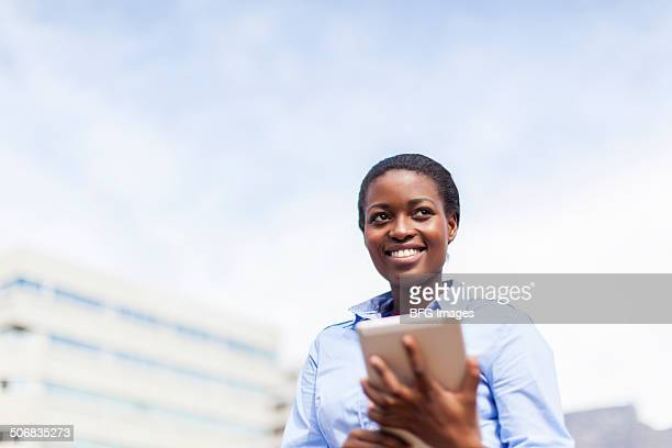 African business woman on the rooftop of a building using a digital tablet, Cape Town, South Africa