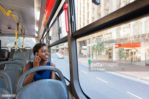 African business woman sitting on bus and looking out of window, using mobile phone, Cape Town, South Africa