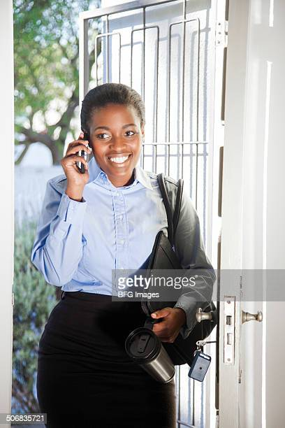 African business woman talking on mobile phone and walking through door into house, Cape Town, South Africa