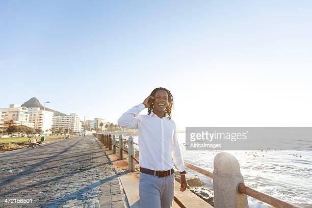 Afroamerikanischer Geschäftsmann im promenade am Strand am Telefon.