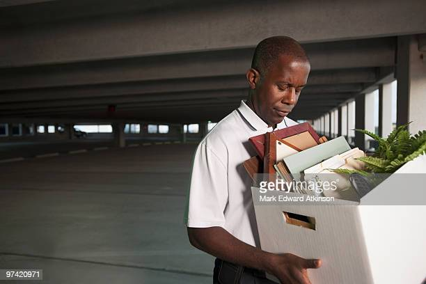 African businessman carrying personal belongings