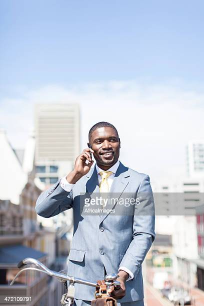 African businessman holding his bicycle and talking on the phone