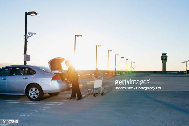 African businessman loading luggage into car