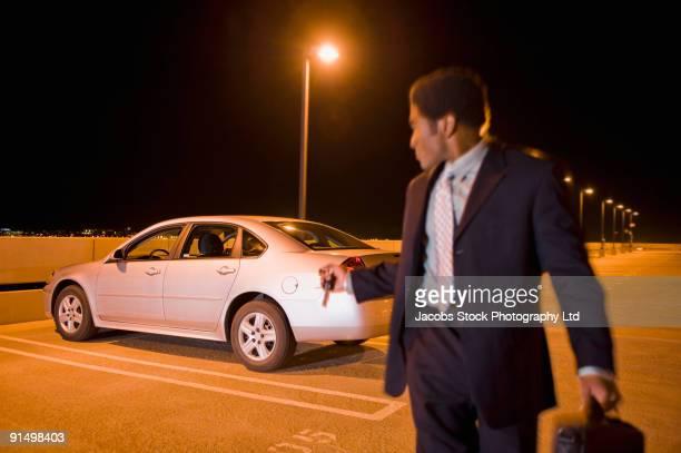 African businessman locking car in parking lot