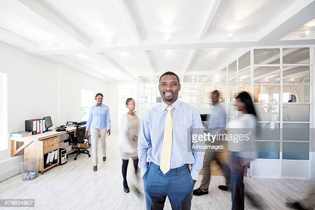African businessman looking at the camera with team in background