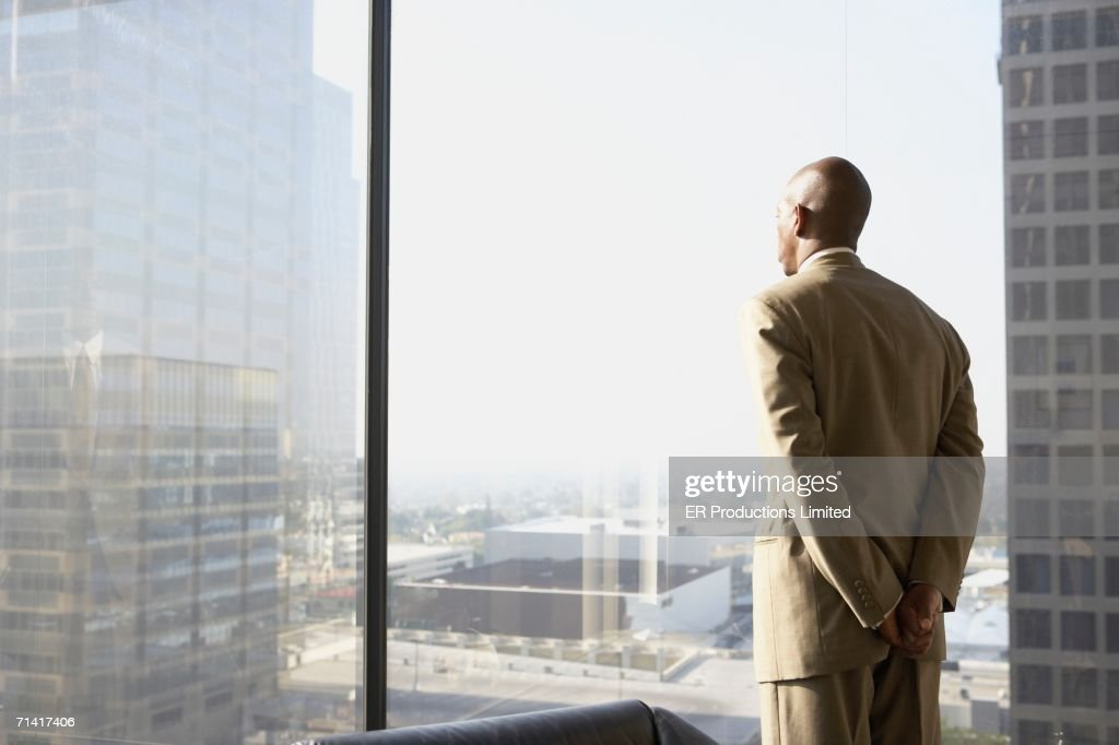 African businessman looking out a window : Stock Photo