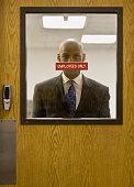 African businessman looking through door