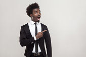 African businessman  pointing finger at copy space, looking at camera with shocked face. Studio shot, gray background