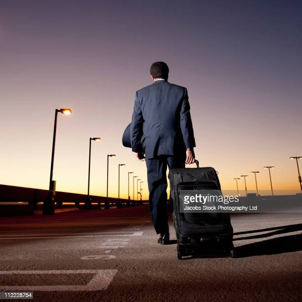 African businessman pulling luggage in parking lot
