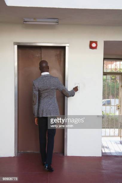 African businessman pushing elevator button