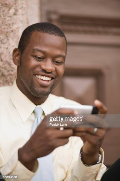 African businessman sending text message