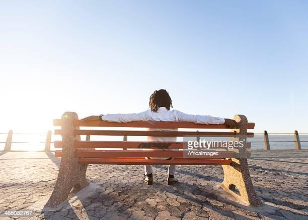 African Homme d'affaires assis et d'attendre le coucher du soleil.