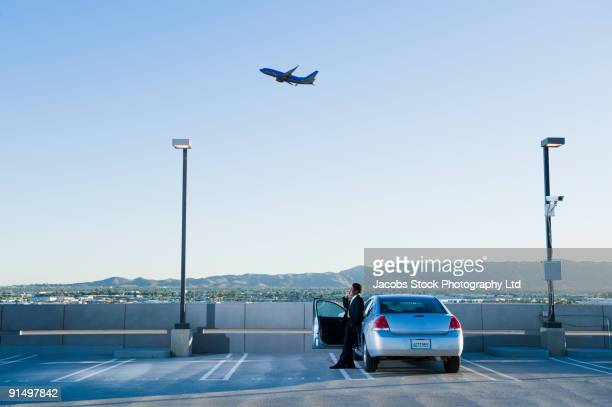 African businessman standing by car at airport