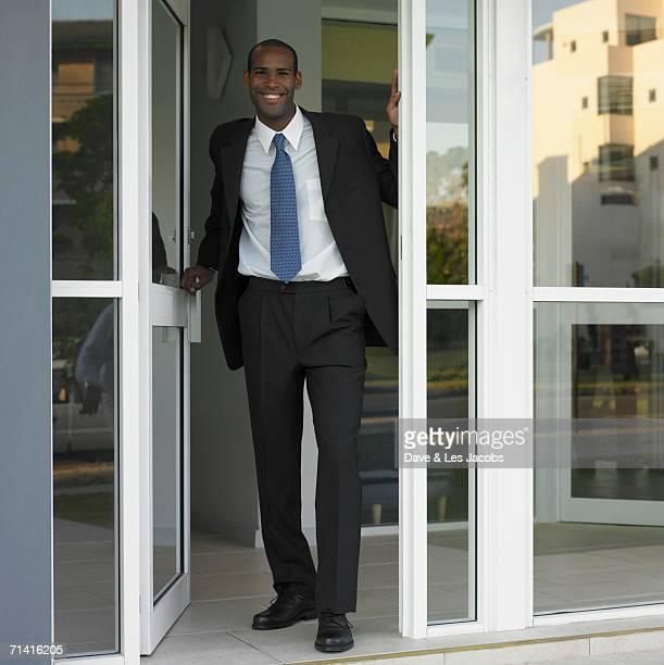 African businessman standing in open door