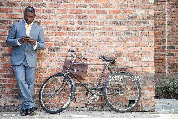 African businessman standing next to his bicycle with crossed legs.