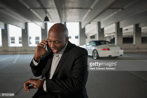 African businessman talking on cell phone in parking garage