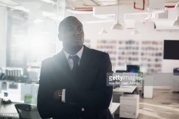 African businessman with arms crossed at the office