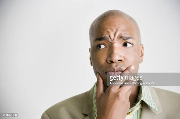 African businessman with hand on chin