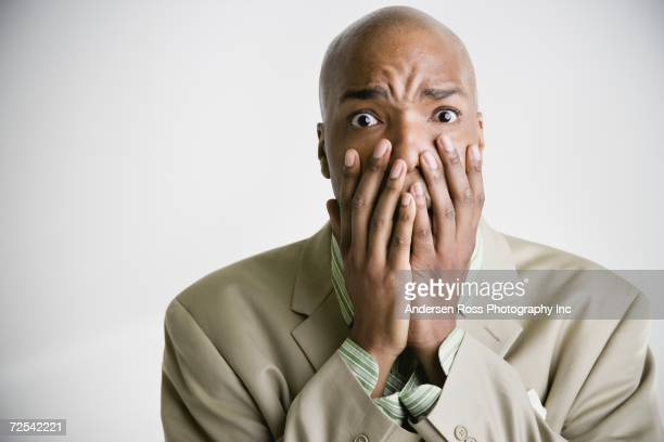 African businessman with hands covering lower half of face