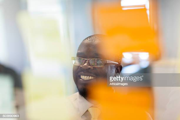 African businessman working from sticky notes.