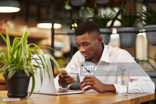 African businessman working with laptop and paying with credit card : Stock Photo