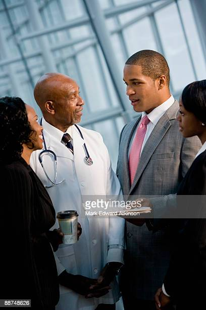 African businesspeople talking to doctor