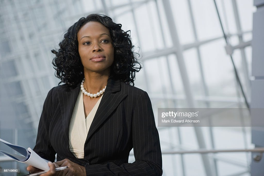 African businesswoman holding paperwork : Stock Photo
