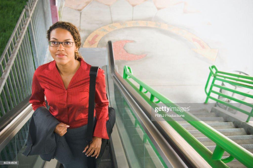 African businesswoman on escalator : Stock Photo