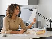 African businesswoman reading paperwork
