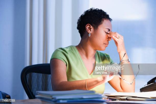 African businesswoman rubbing eyes