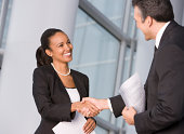 African businesswoman shaking hands with co-worker