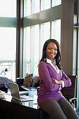 African businesswoman sitting on edge of desk