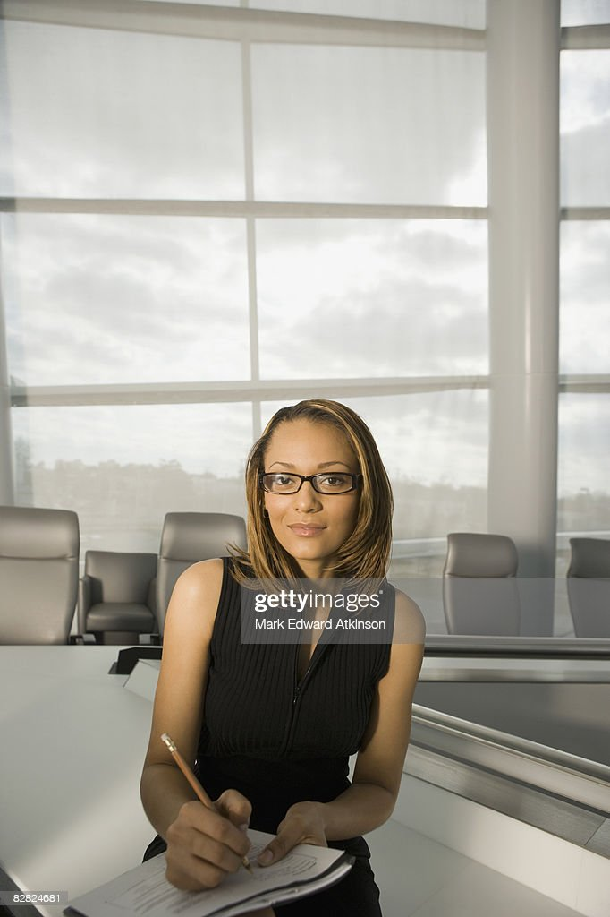 African businesswoman taking notes in conference room : Stock Photo