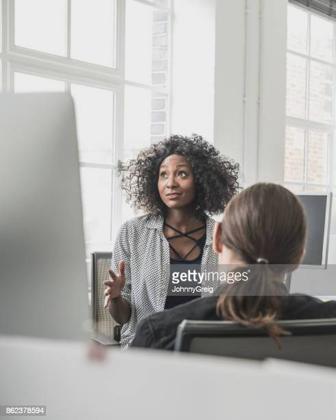 African businesswoman with Afro hairstyle looking away and explaining to male colleague