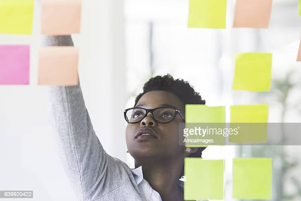 African businesswoman working from sticky notes.