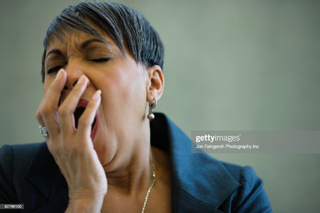 African businesswoman yawning