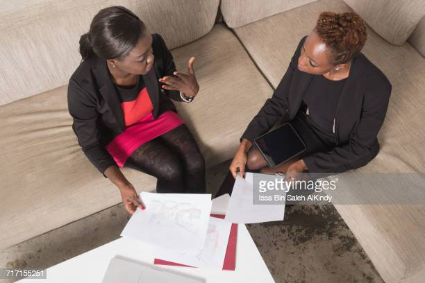 African businesswomen discussing over documents in office