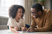 Cute african american child girl enjoying drawing with colored pencils having fun talking to black dad baby sitter, happy family father and kid daughter laughing play together lying on floor at home