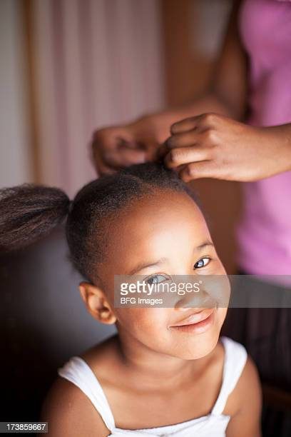 African child having hair styled
