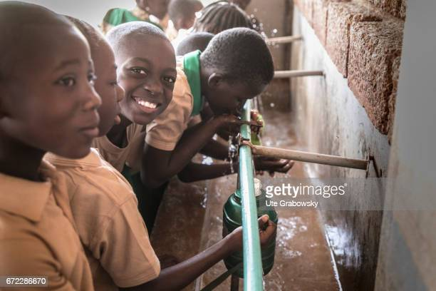 African children at a drinking water dispenser in a school of the Dreyer Foundation Here children are cared for and will be promoted The school is...