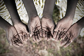 Poor African children keeping their cupped hands up, asking for help. Many African children suffer from poverty, diseases, contaminated water and malnutrition.
