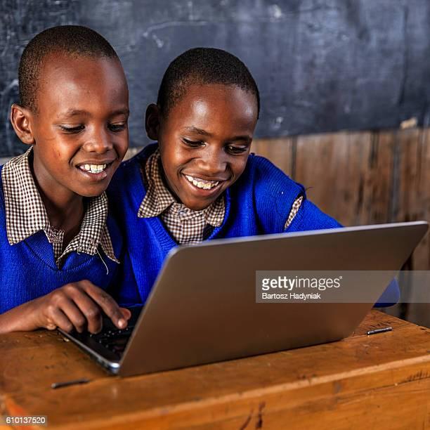 African children using a laptop inside classroom, Kenya