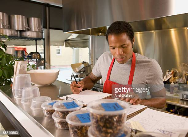 African cook with paperwork in commercial kitchen
