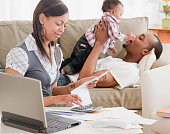 African couple and toddler paying bills in living room