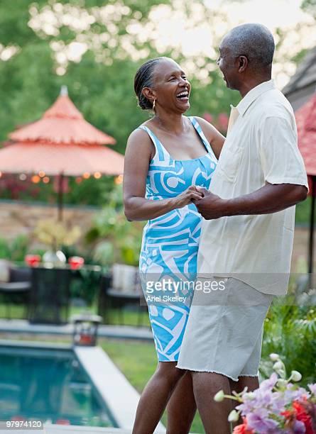 African couple dancing in backyard