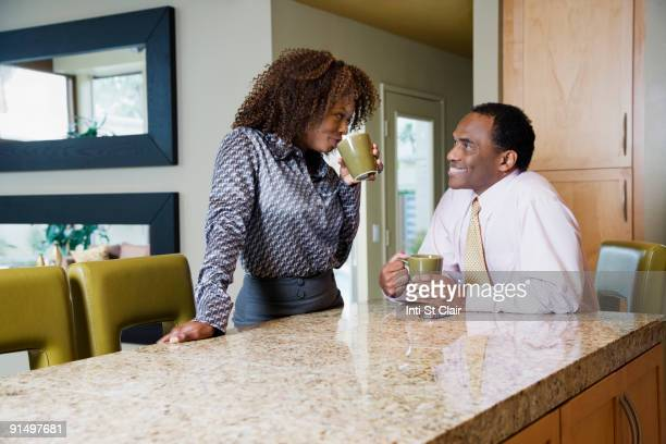 African couple drinking coffee in modern kitchen